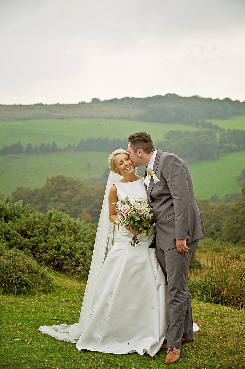 Groom kisses bride on Dartmoor in front of Brentor Church