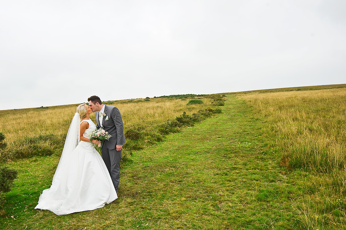 Bride and groom kissing on open Moorland on Dartmoor