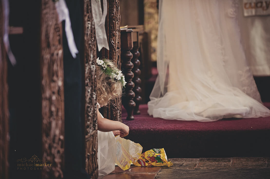Flowergirl seated on floor of the church eats sweets from a bag during the wedding service near Bideford in North Devon.