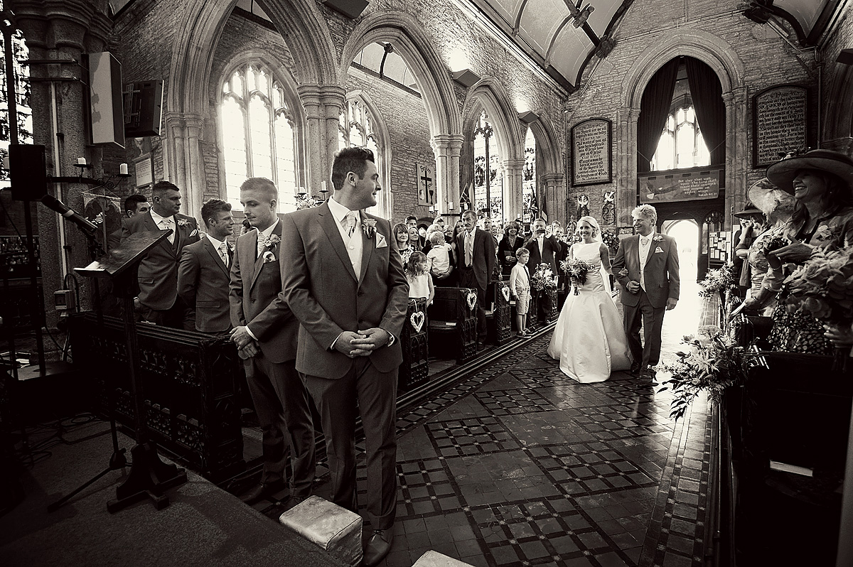 Black and white photo of grooms first look of bride in Buckland Monochorum church in Devon