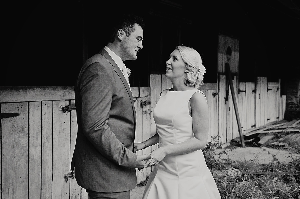 Bride looking at each other whilst holding hands on Dartmoor farm