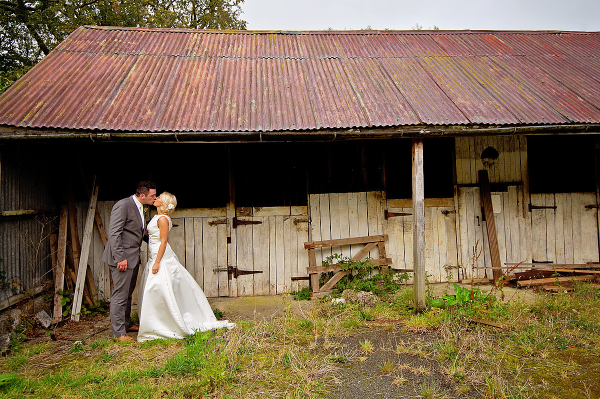 Bride and groom kissing in front of old stables on Dartmoor