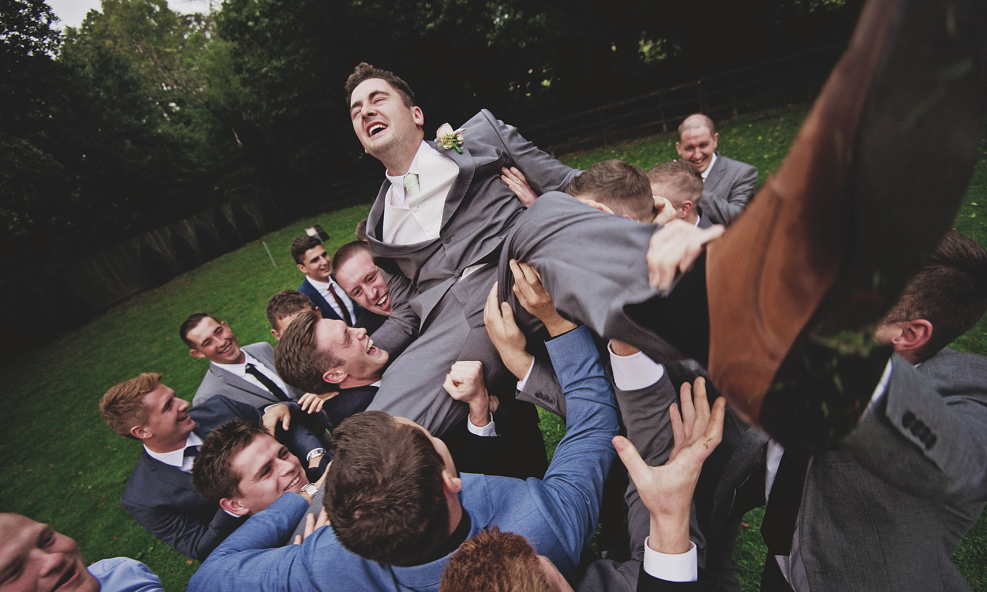 Groom being held aloft by his friends on his wedding day - documentary photo