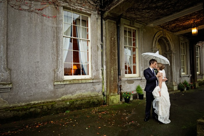 Bride and groom kiss under a white umbrella in front of North Devon country house entrance.