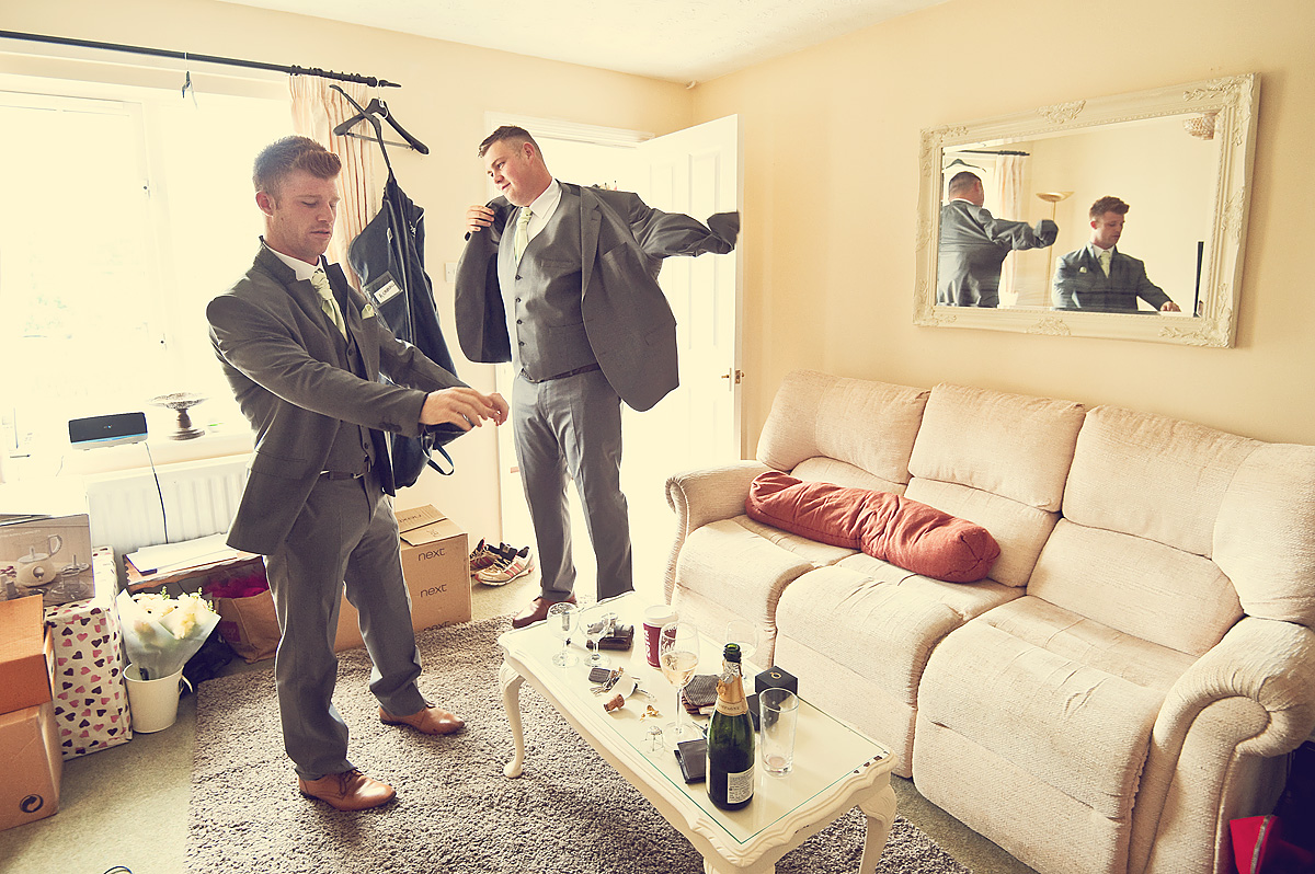 Wedding usher opening champagne whilst getting dressed