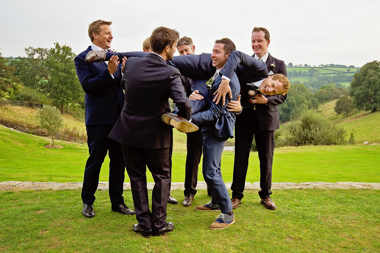Ushers almost drop the groom at outddor wedding in Devon