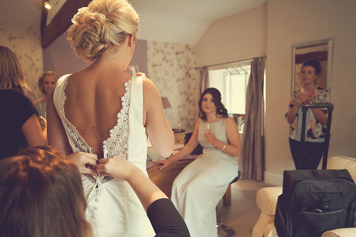 Bride having weddign dress buttoned up at Dartmoor wedding