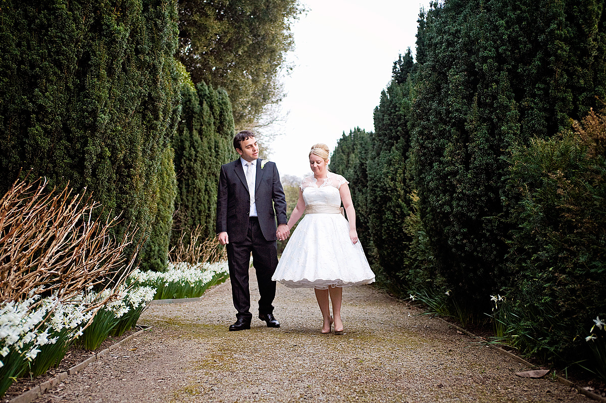 Bride and groom walking in formal gardens at Hotel Endsleigh in Devon