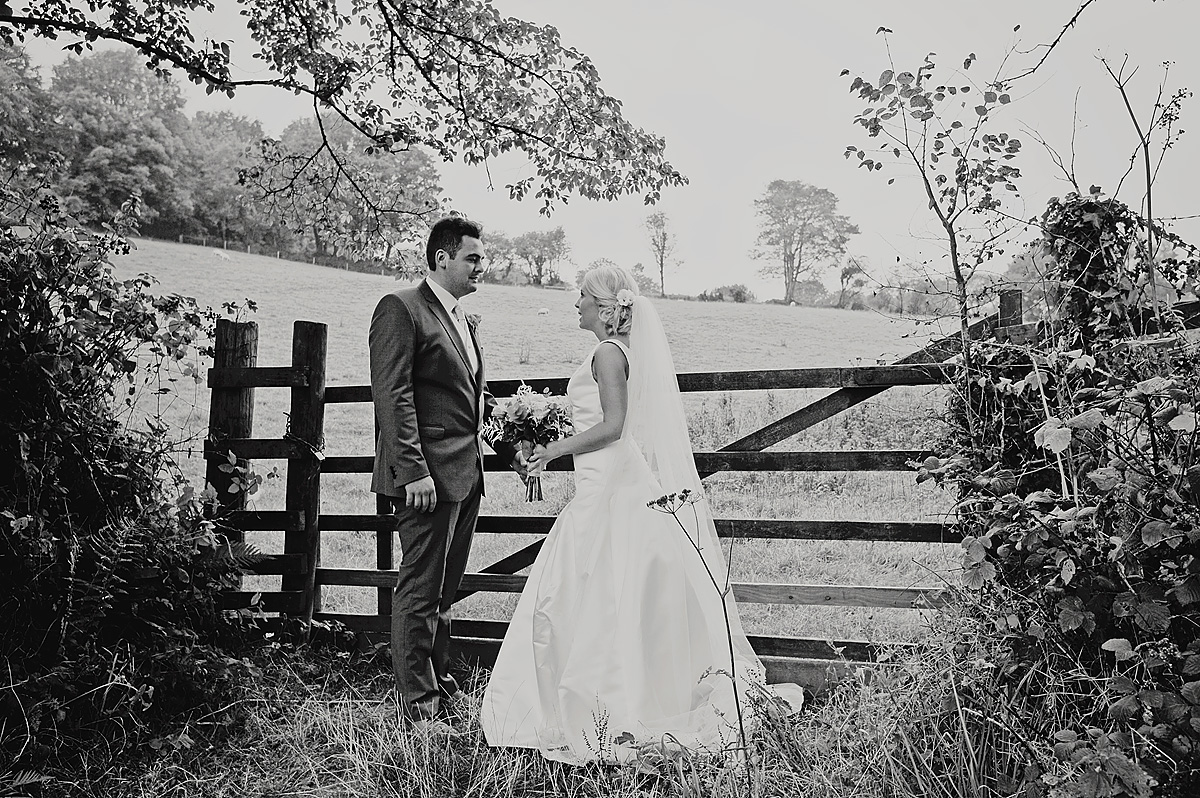 Bride and groom in front of Dartmoor farm gate in black and white