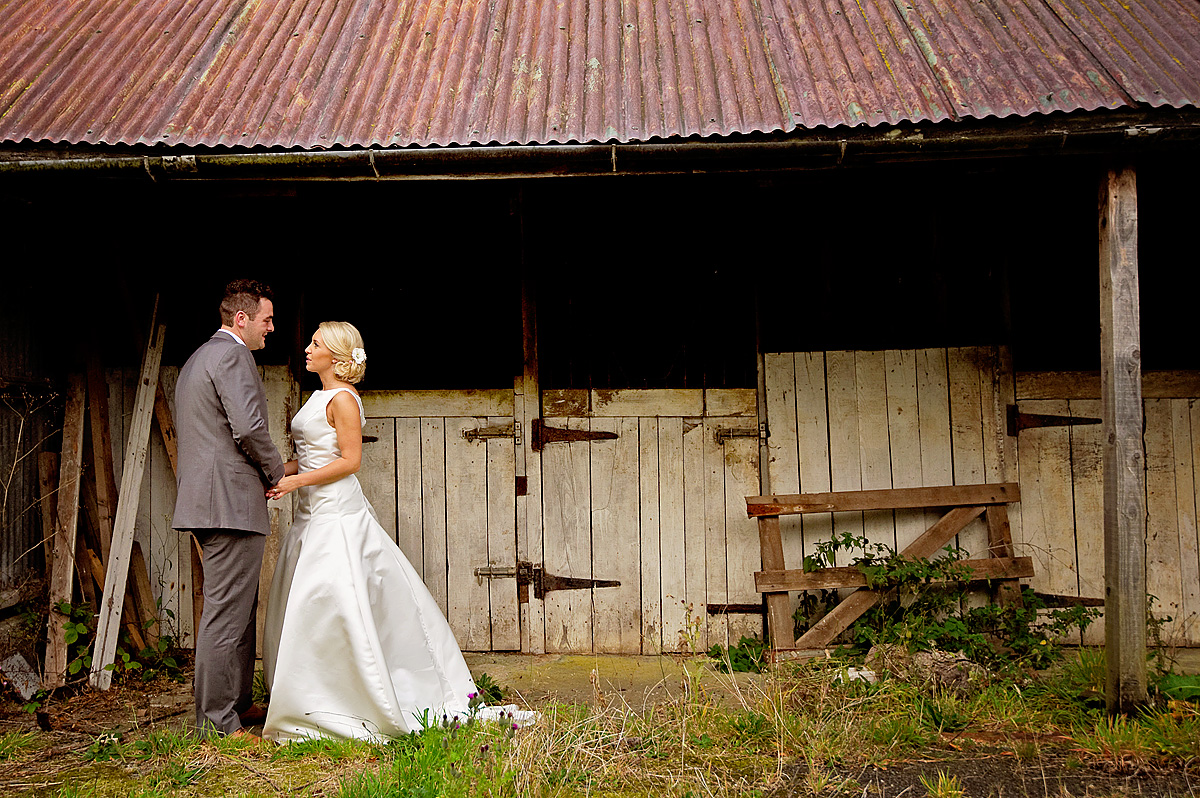 Bride and groom in front of rustic farm stables Lydford