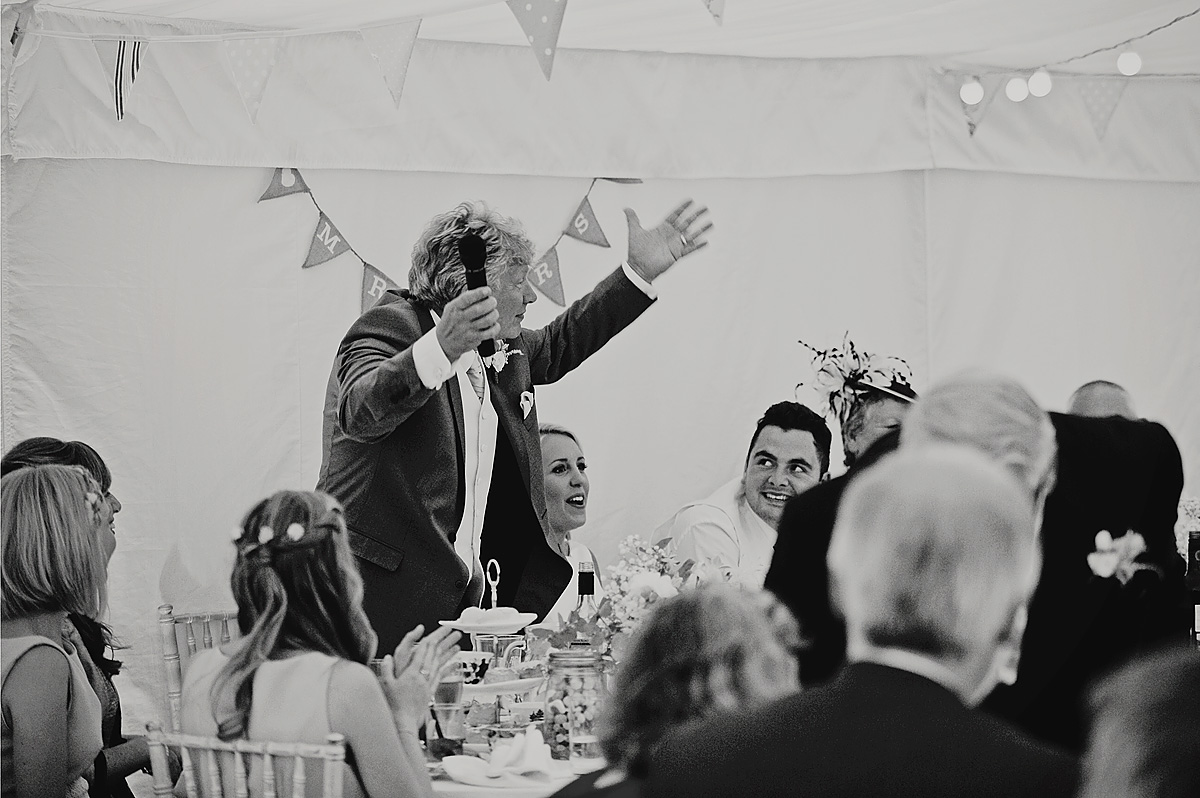 Father of bride giving wedding speech with arms aloft