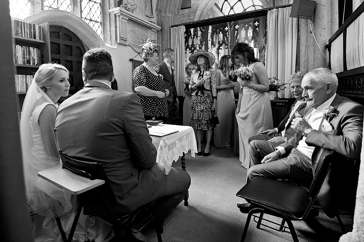 Bride and groom and wedding party signing wedding register in Devon church