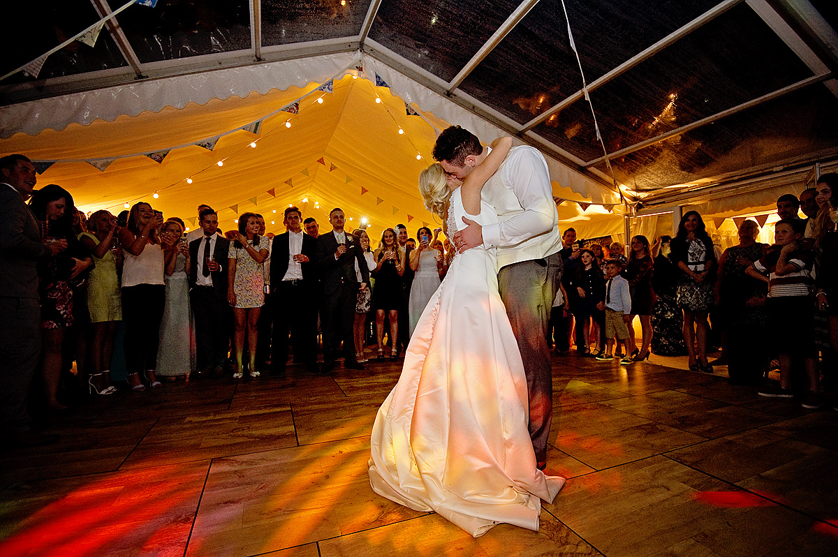 Bride and groom embrace during first dance in wedding marquee on Dartmoor