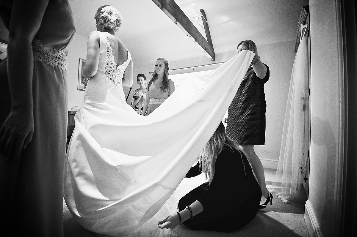 Wedding dressmaker making adjustments under bride's dress