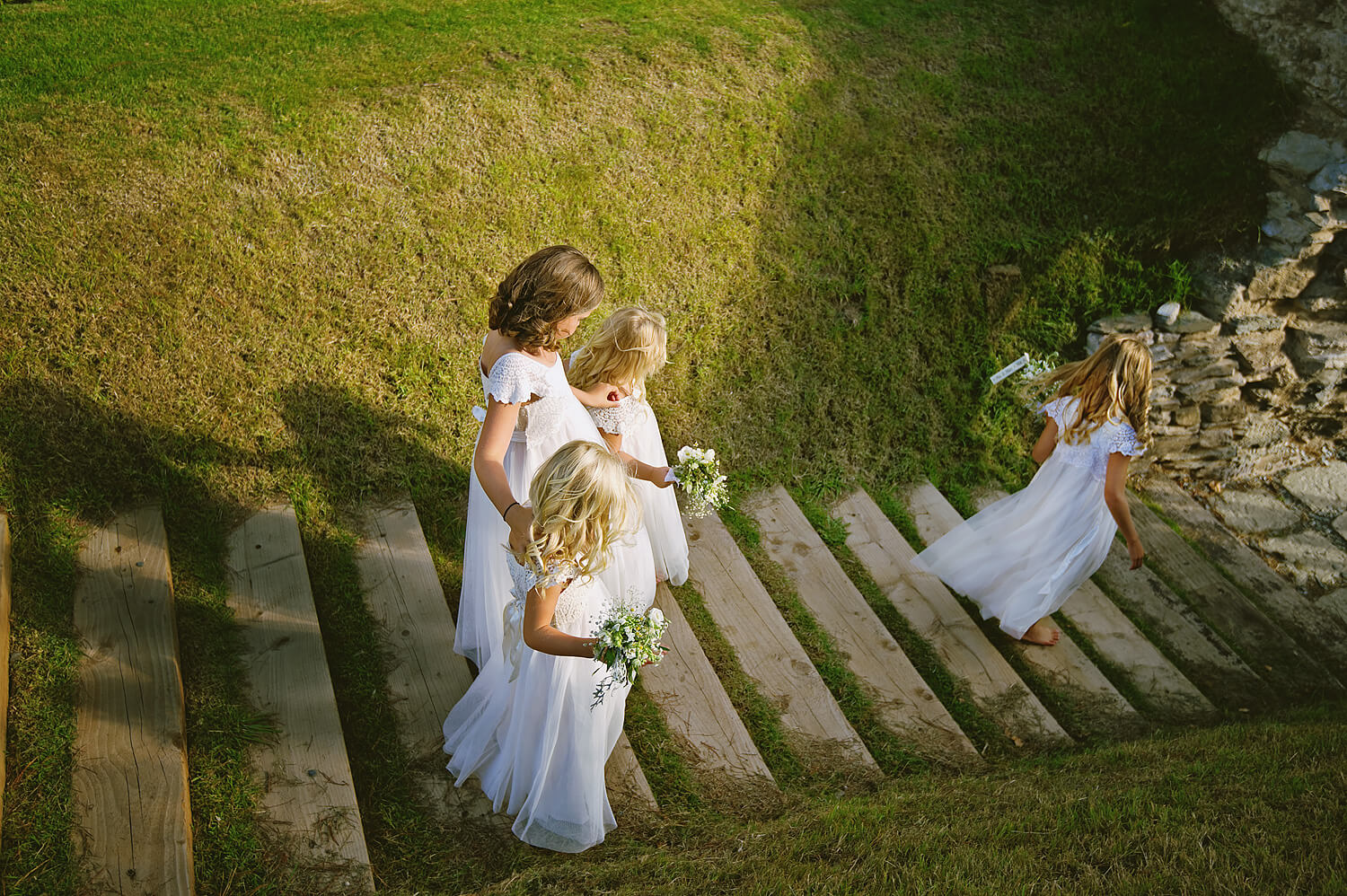 Flowergirls walk dowen the steps at weddings in Cornwall at Polhawn Fort