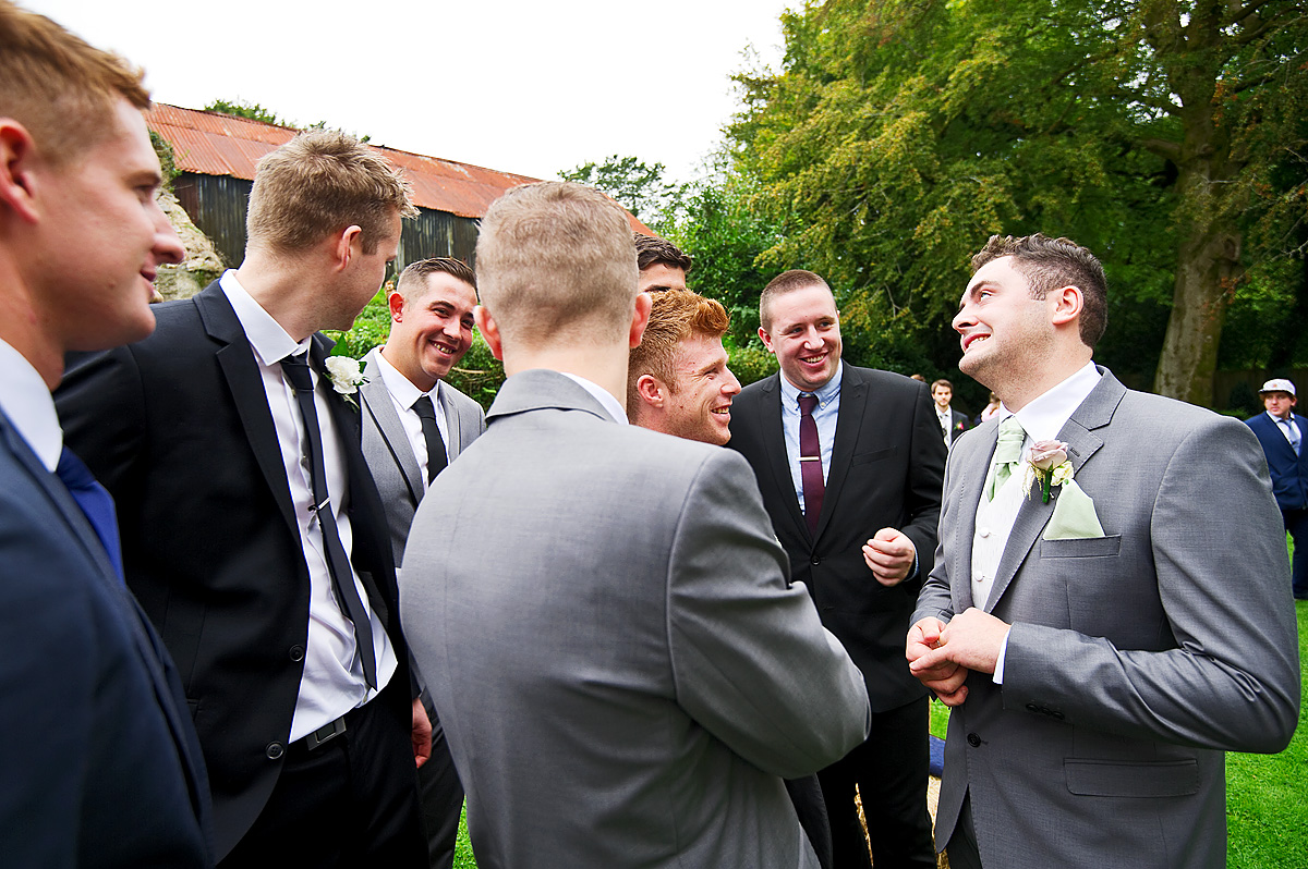 Groom with friends outside on his wedding day