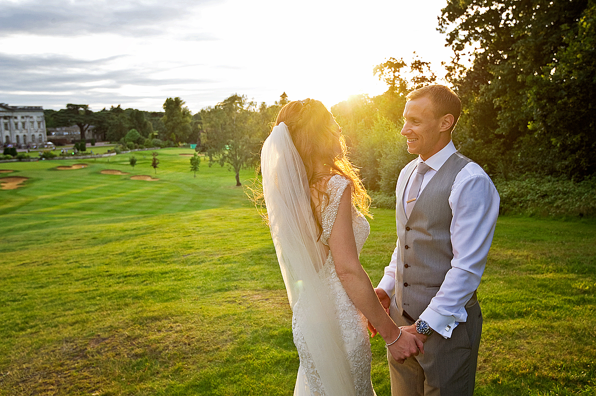 Bride and groom at sunset looking over Moor Park near London