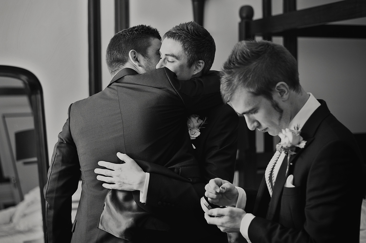 Black and white photos of Bestman checking the wedding rings whilst the groom embraces one of his groomsmen in the background.