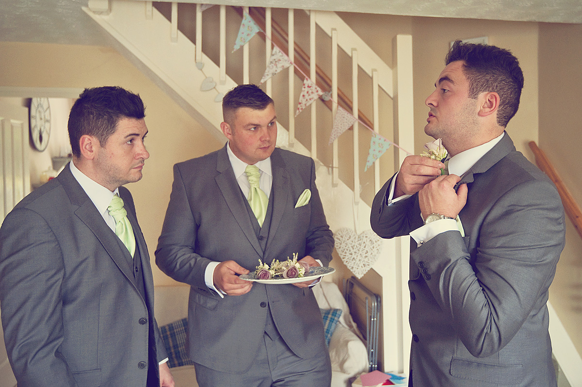 Groom putting buttonhole flower on his suit before wedding