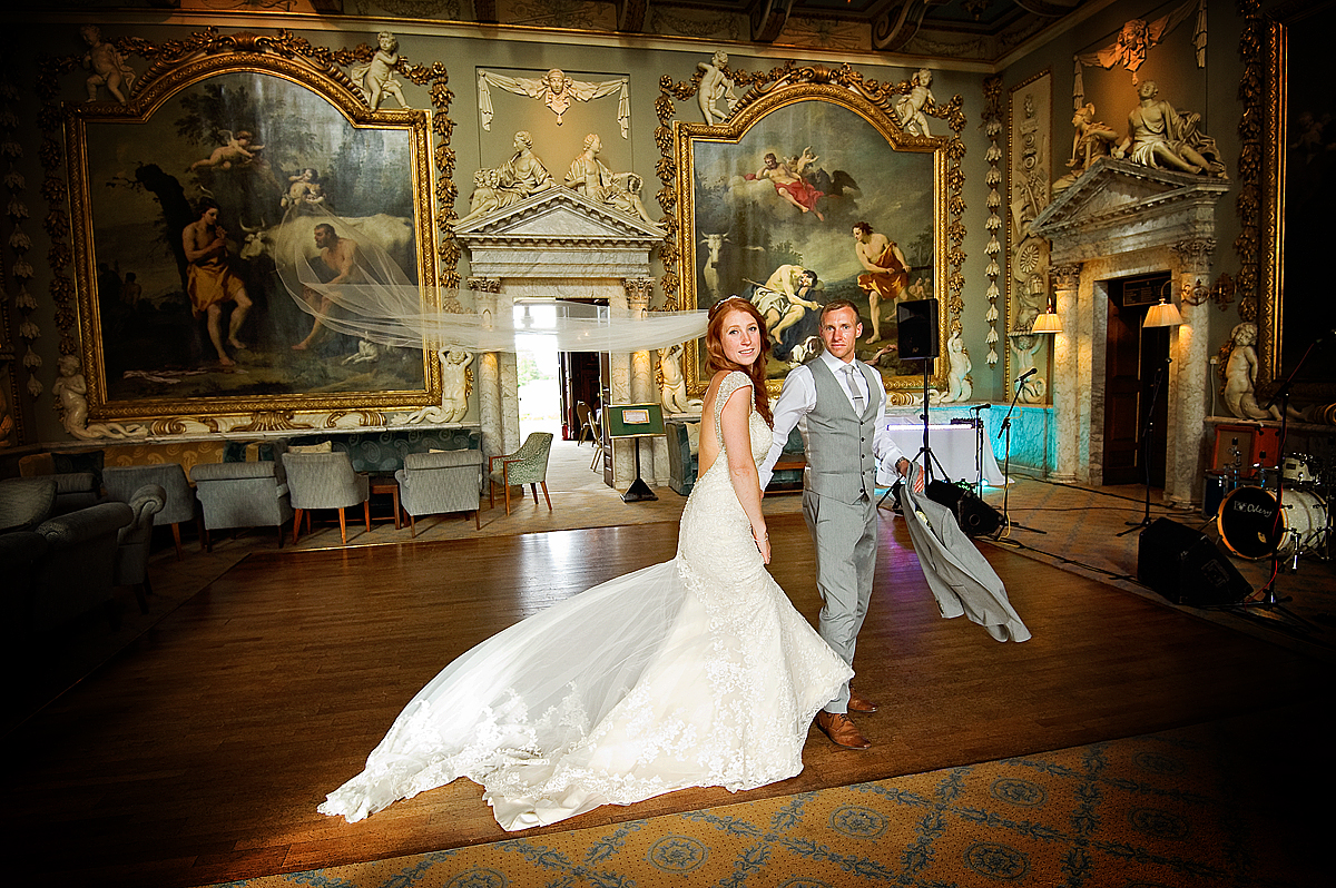 Brides veil blows back as couple walk through hall at Moor Park in London