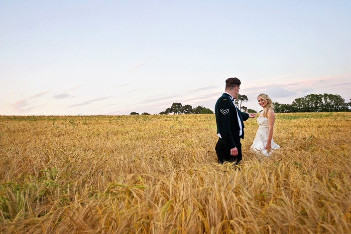 Bride and groom in a corn field on their weddign day