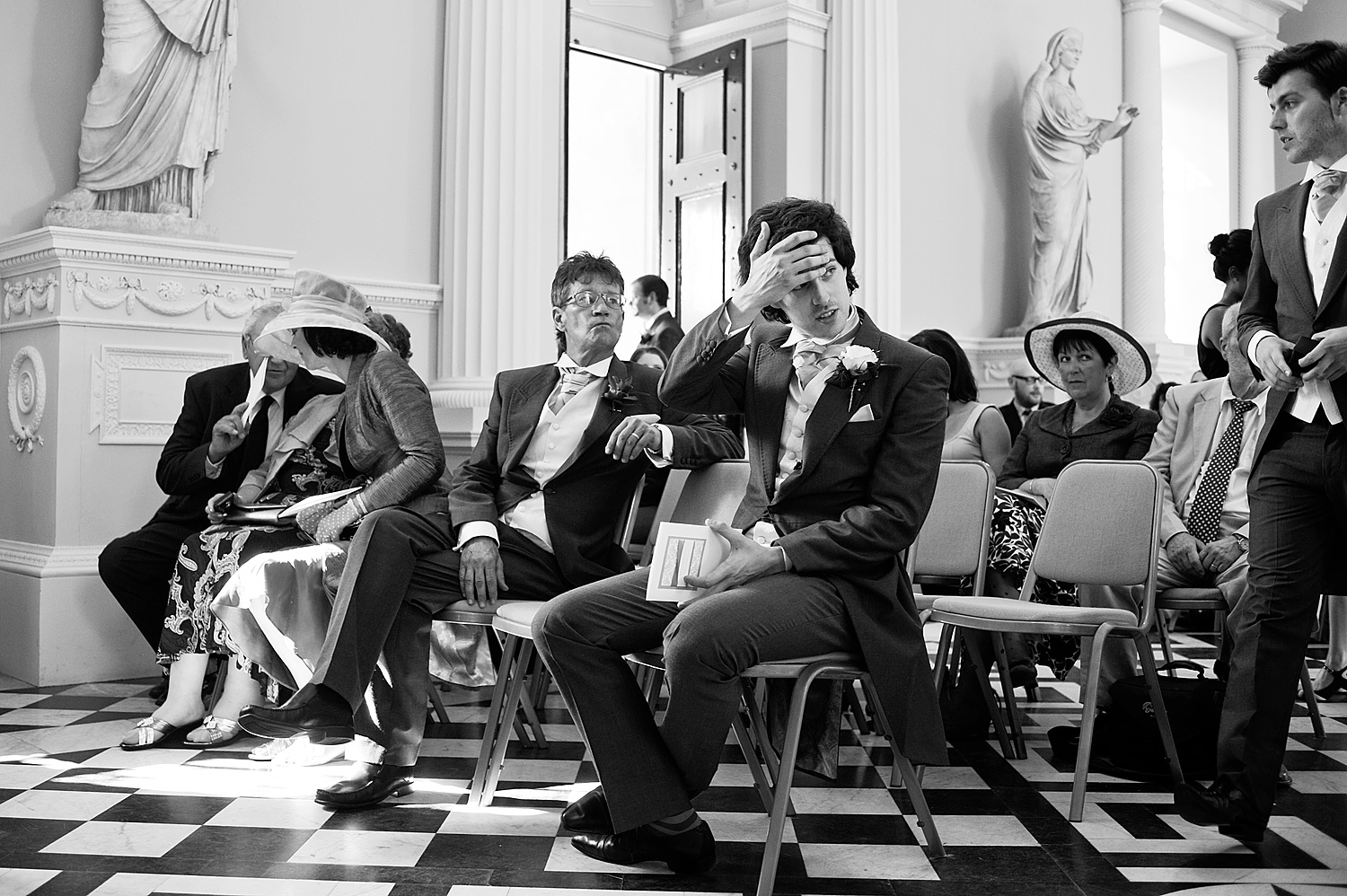 Groom wiping his brow before the wedding ceremony in hall at Syon Park