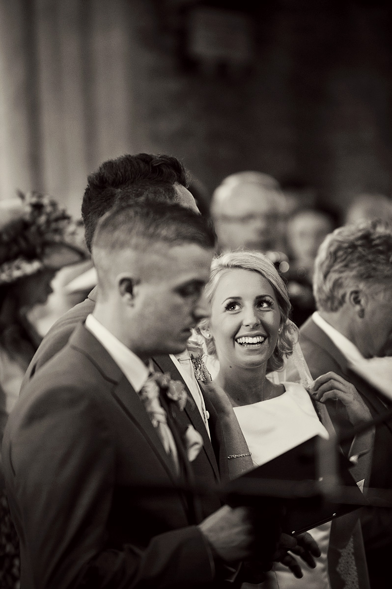 Bride looking and smiling at groom in Church