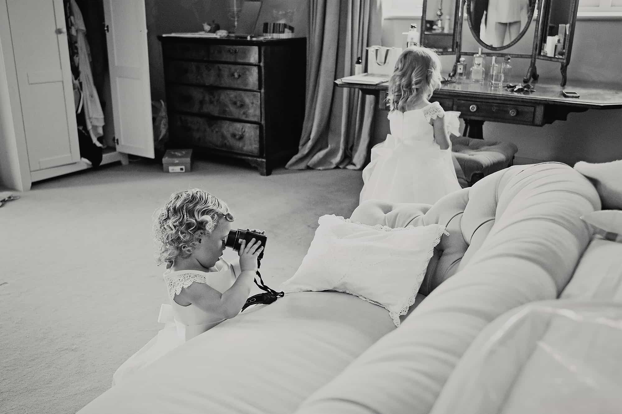 Flowergirl trying to take wedding photos with at camera at Dorset wedding at Axnoller House