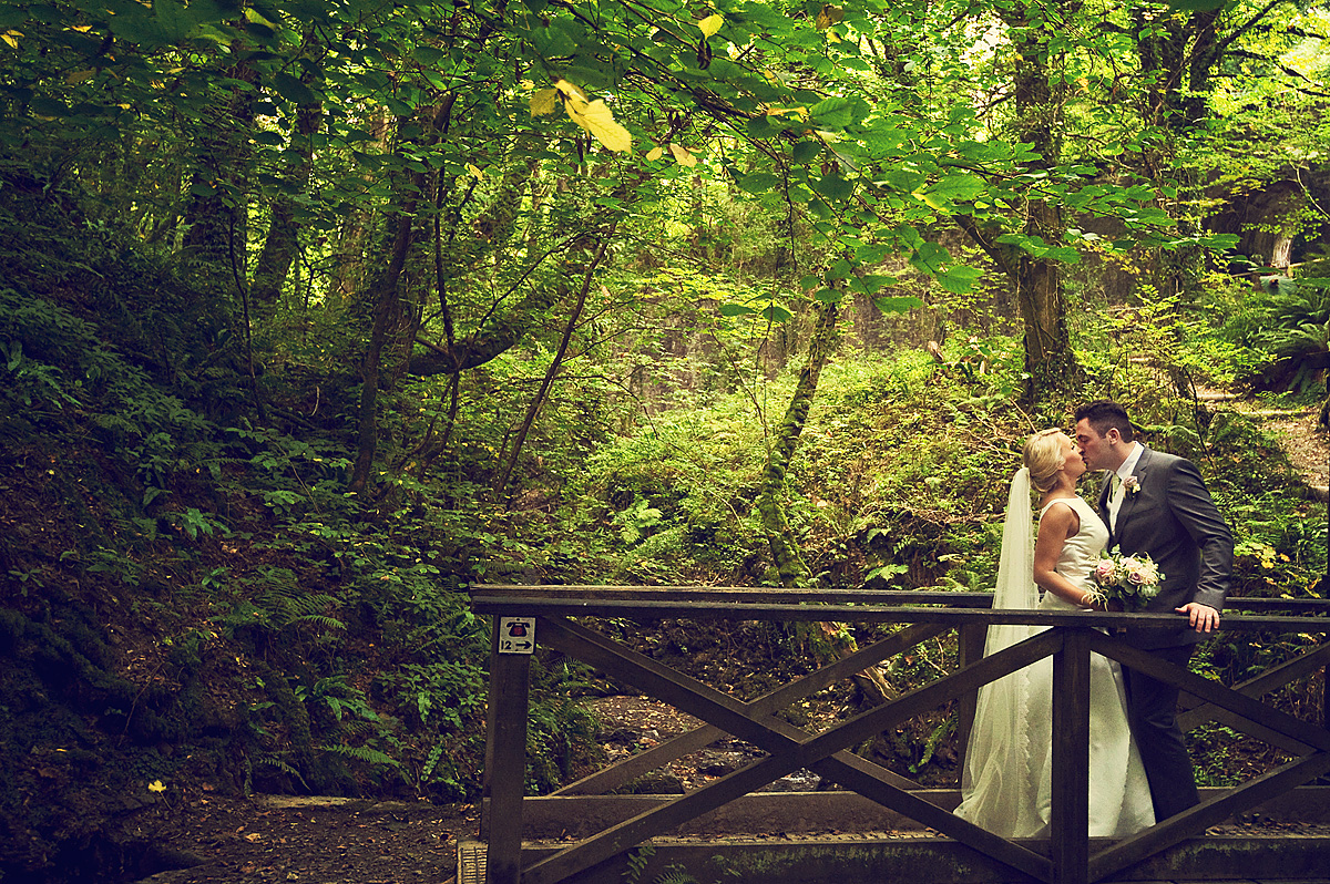 Bride and groom kiss on bridge at Lydford Gorge on Dartmoor