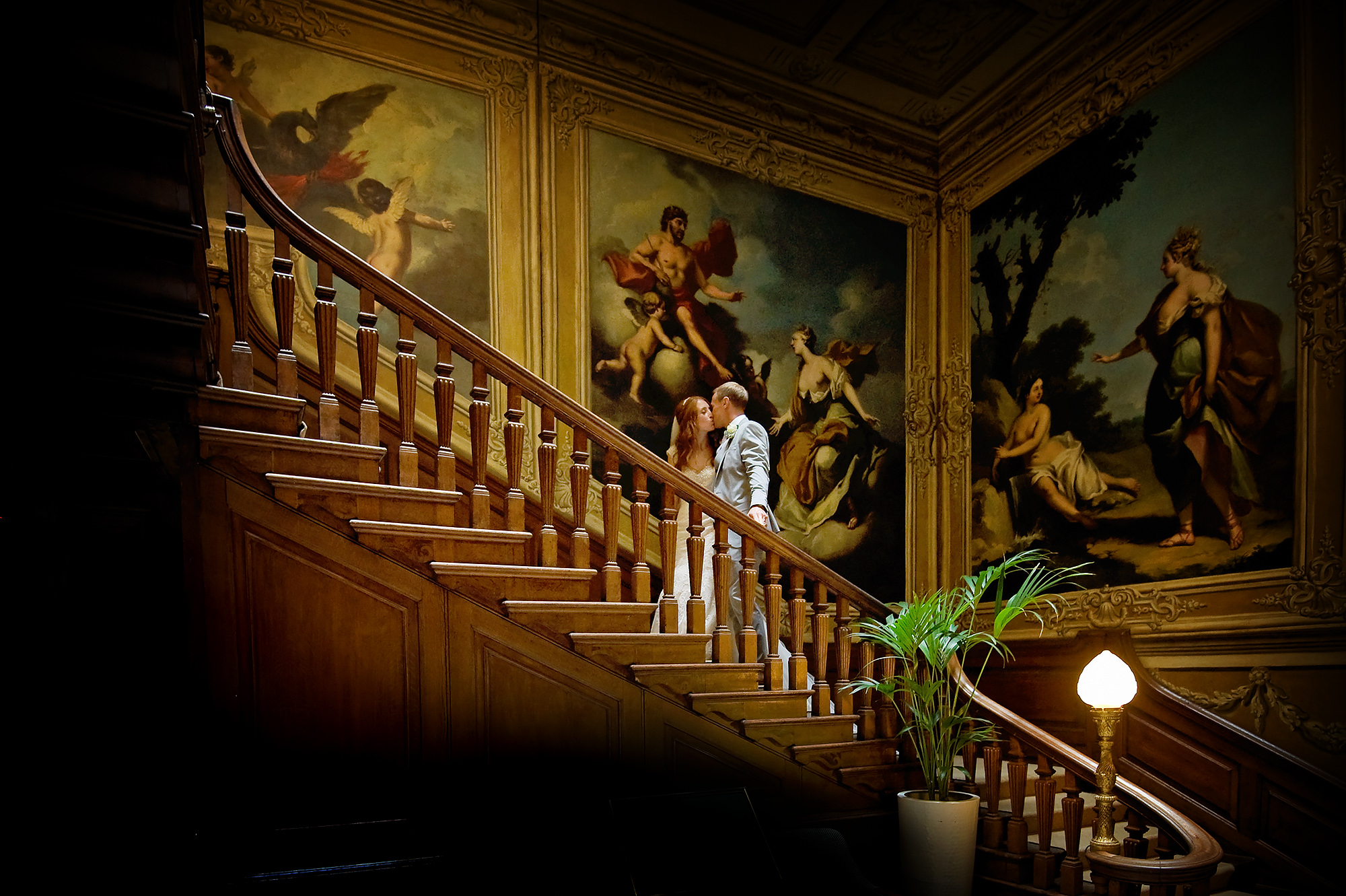 Bride and groom kiss on the main staircase at luxury London wedding venue Moor Park