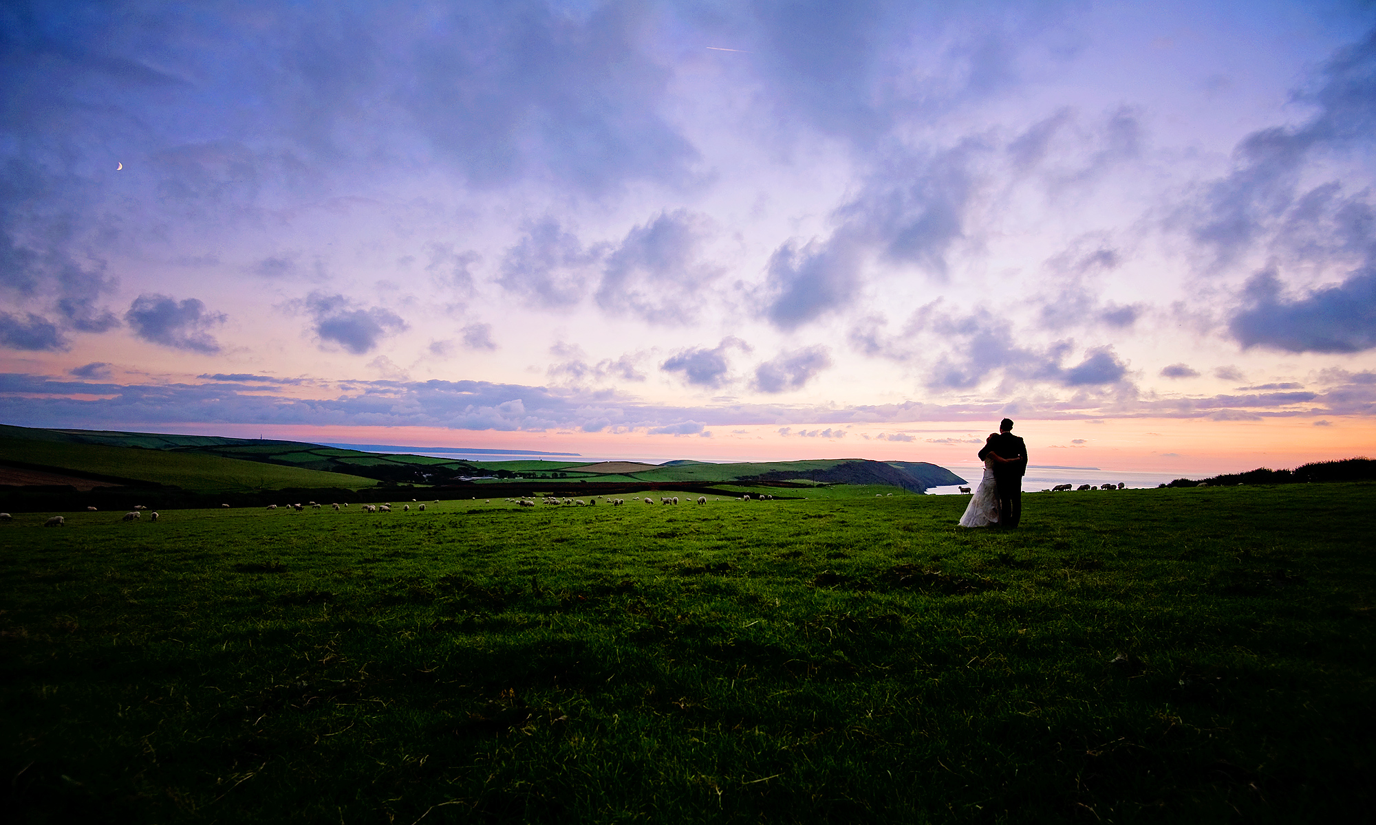 Bride and groom looking over the Atlantic Ocean in North Devon at sunset