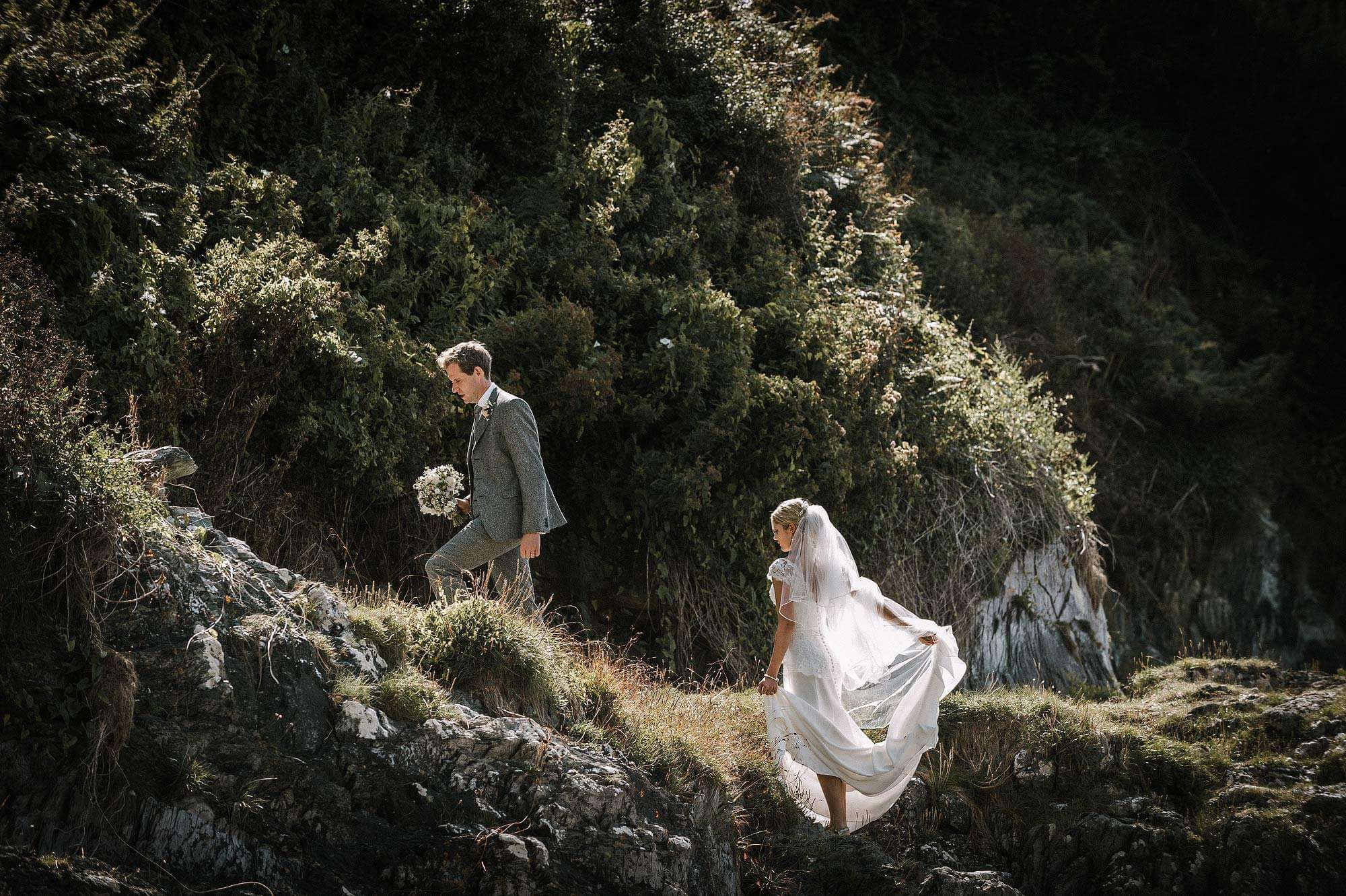 Vintage Bride and groom walk up from the beach at polhawn Fort in cornwall