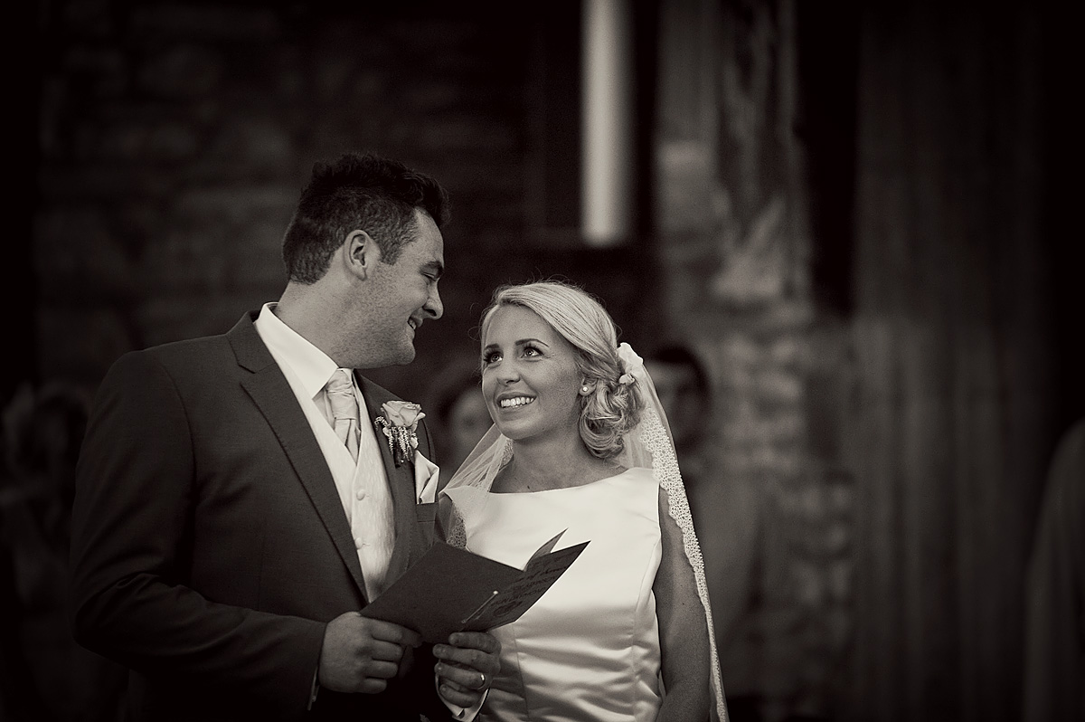 Bride looks into grooms eyes during Devon church wedding