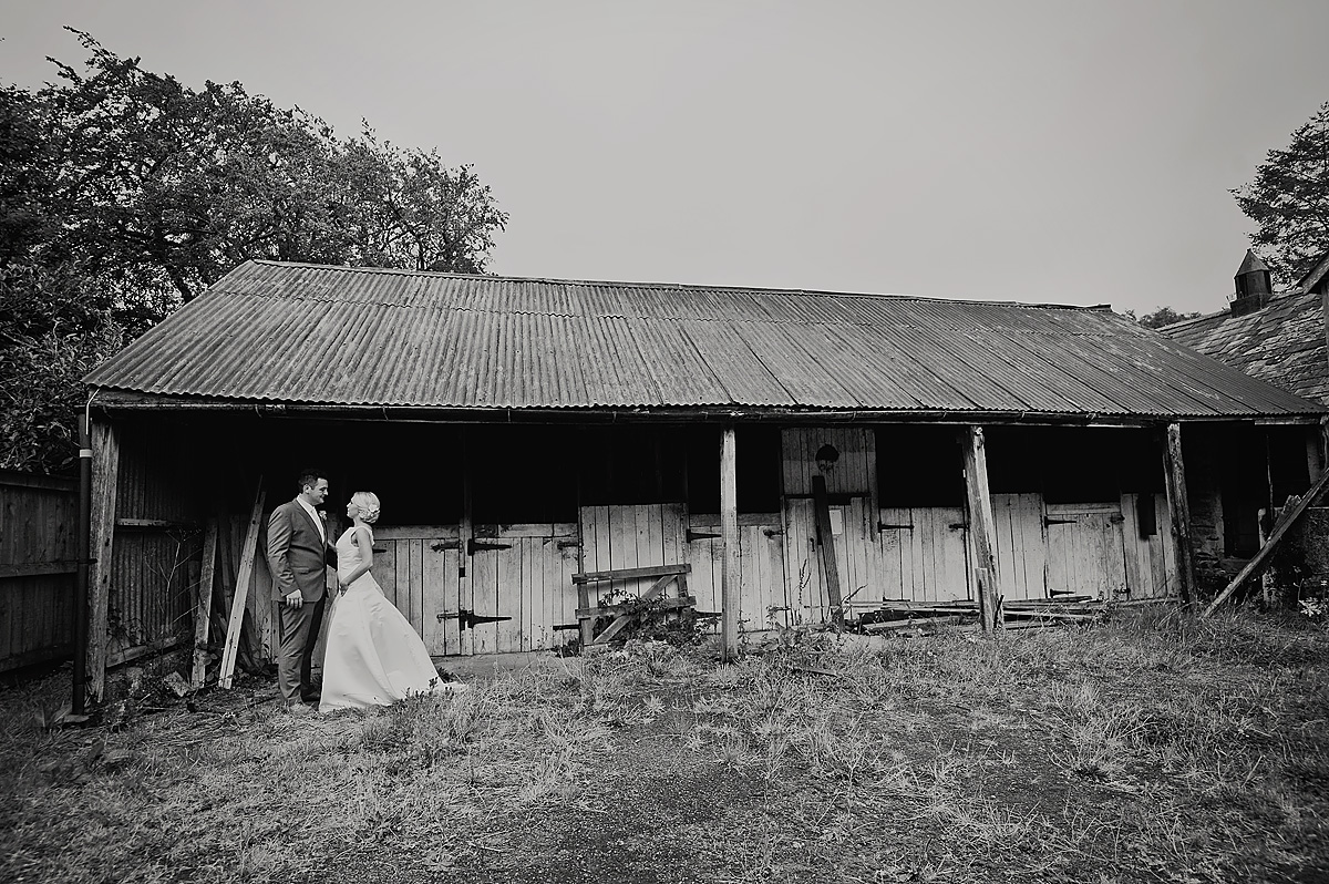 Black and white photo of wedding couple in front of rustic Dartmoor barns