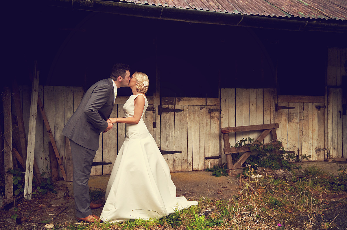 Bride and groom hold hands and kiss in front of Dartmoor rustic stables