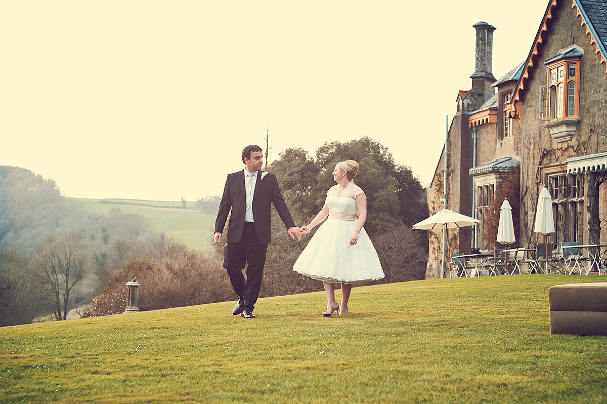 Bride and groom walking on path outside Hotel Endsleigh