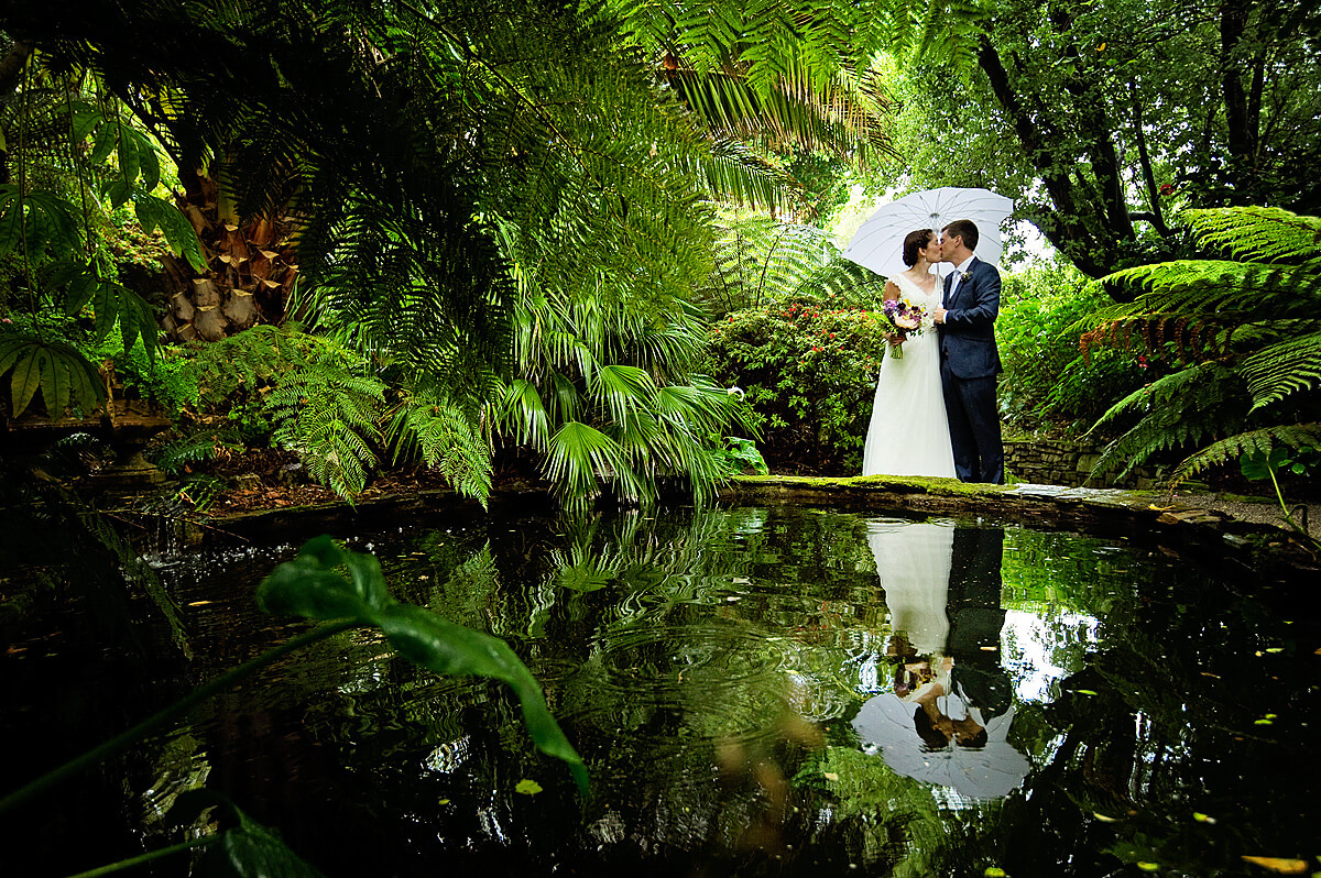 Bride and groom kiss in front of the tropical garden pond at Lamorran House Gardens in St Mawes Cornwall.