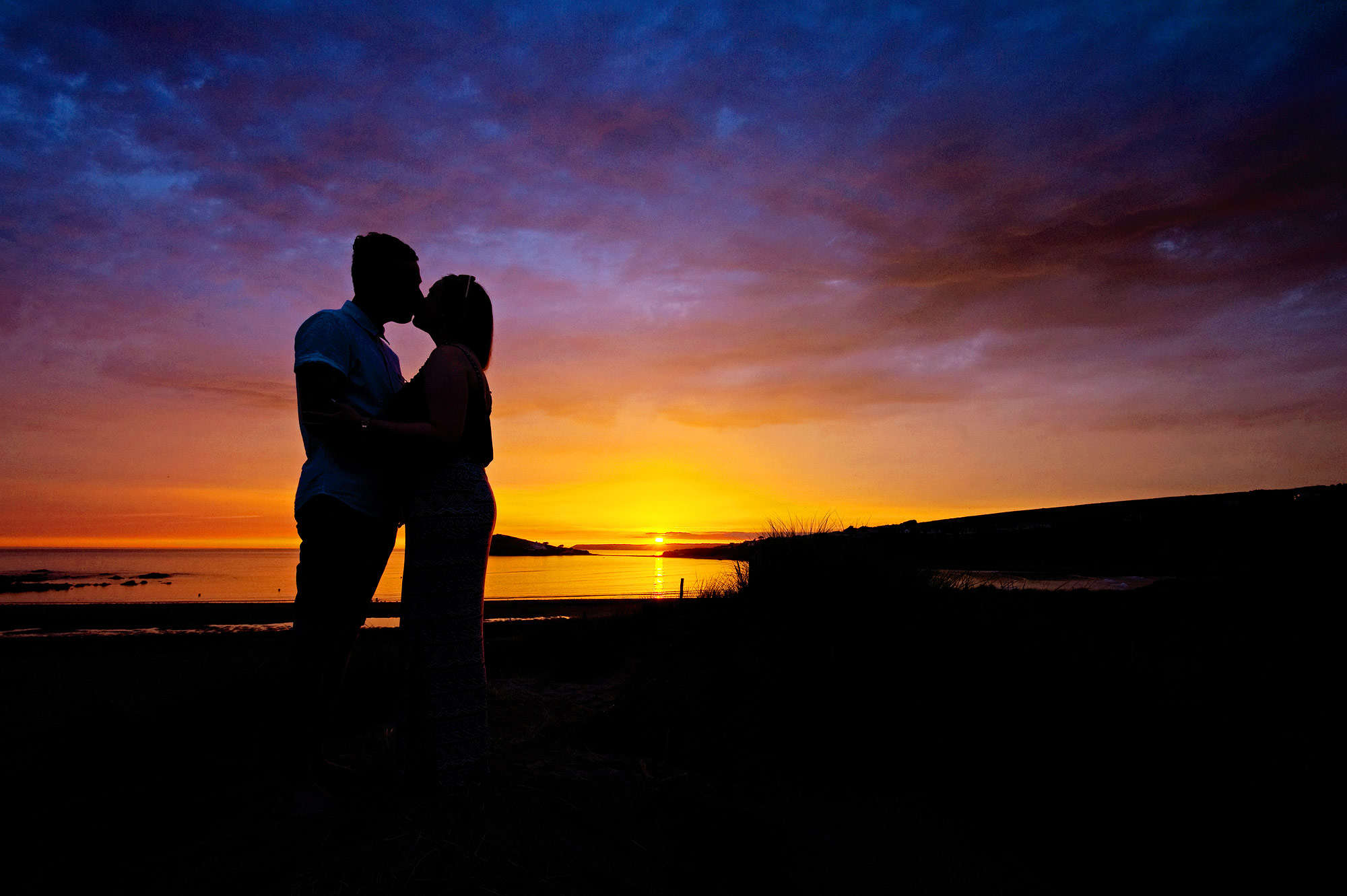 Engaged couple kiss at sunset at Bantham Beach in Devon with Burgh Island in the background.