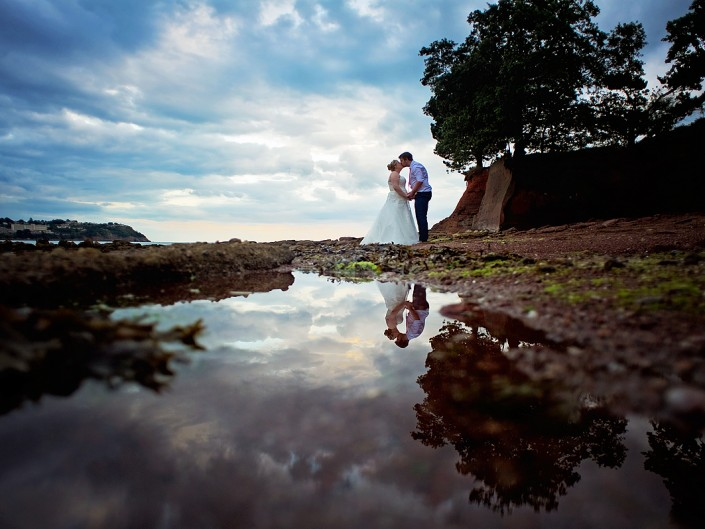 Bride and groom reflected in a rock pool at Torquay beach wedding.