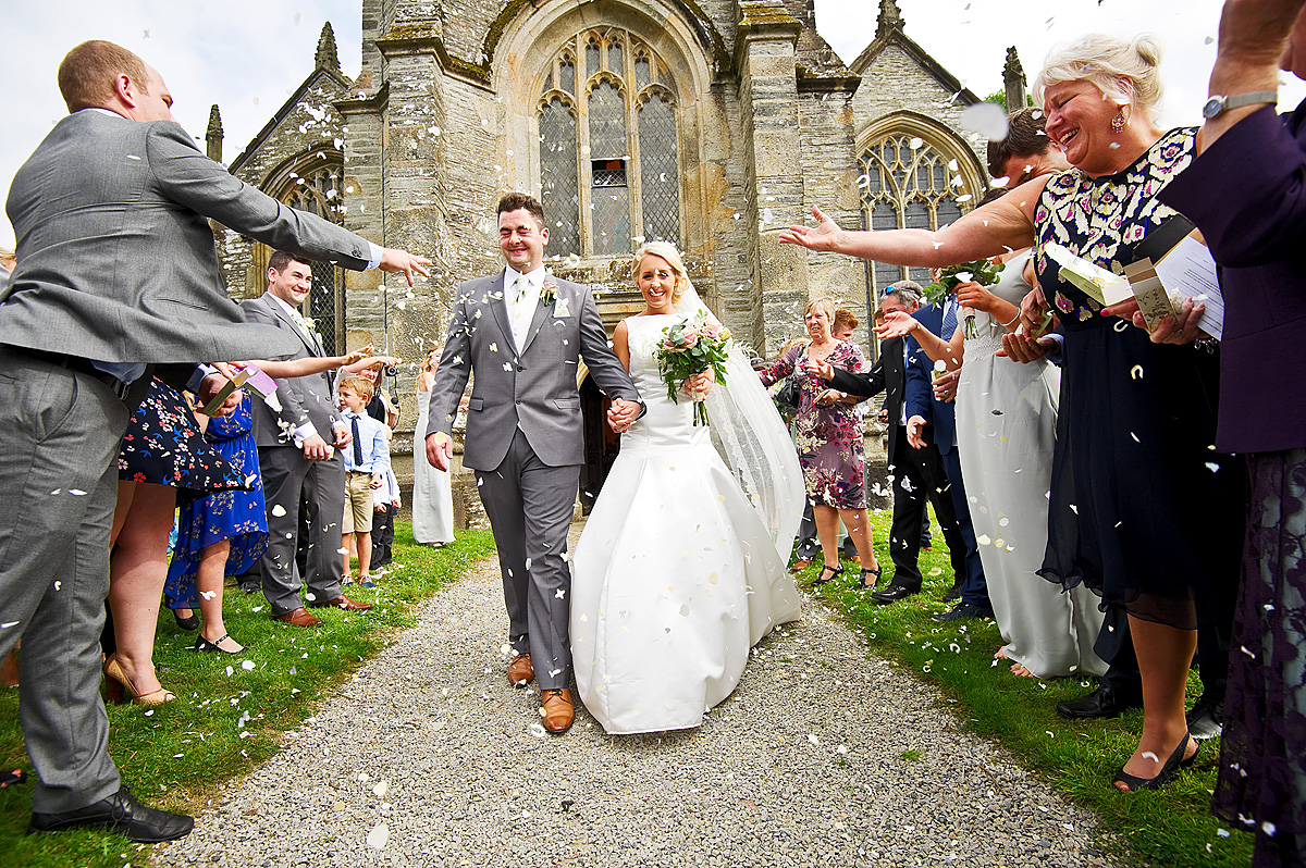 Guests throwing confetti at bride and groom outside Buckland Monachorum church in Devon
