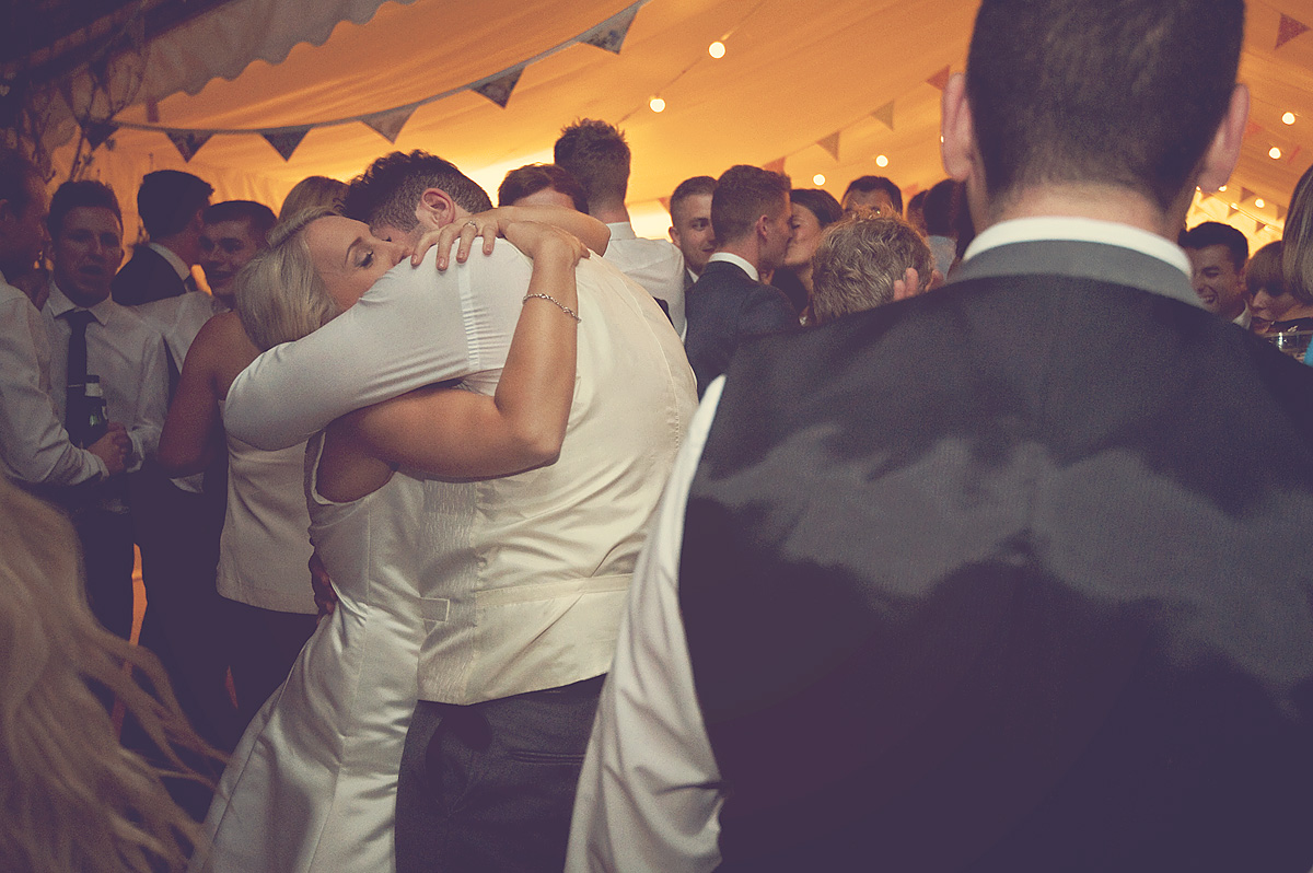 Bride and groom embrace on dancefloor