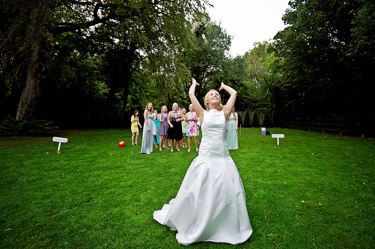Bride has just thrown wedding bouquet and women guests wait to catch it