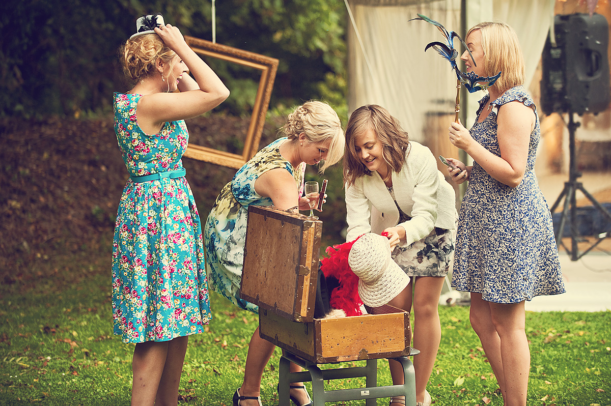 Four wedding guests look for props in photobooth suitcase