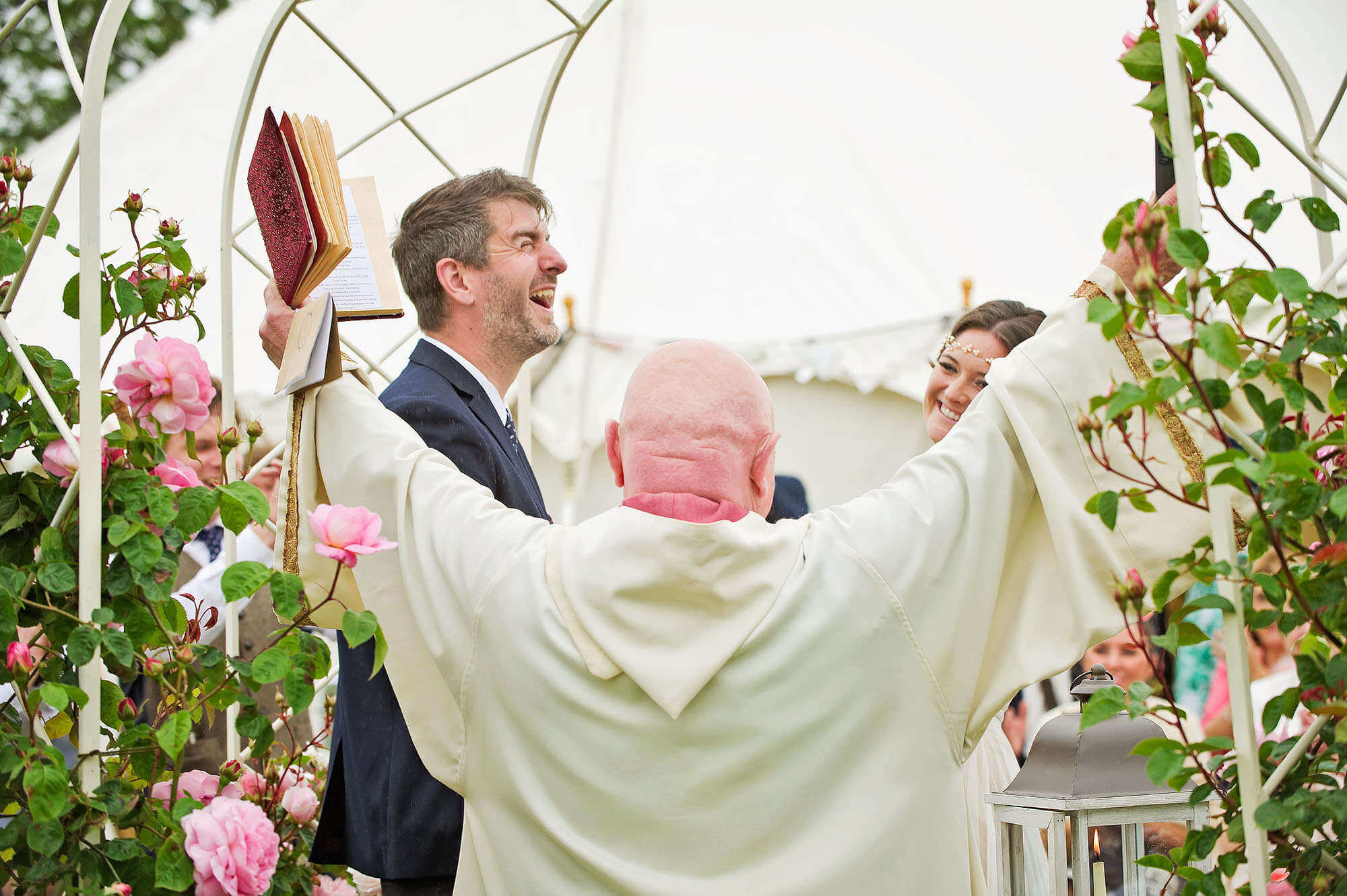 Very happy groom and excited vicar at an outdoor wedding in Devon