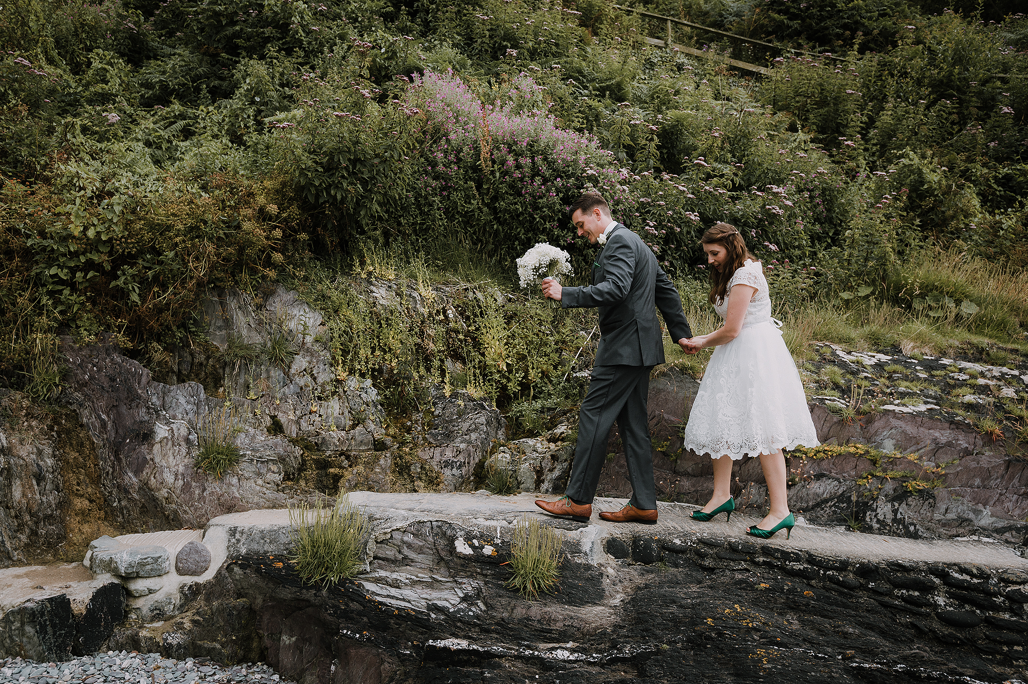 Bride and groom walking across rocks in Cornwall wedding