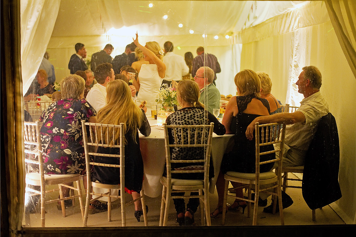 Wedding guests seen through marquee windows