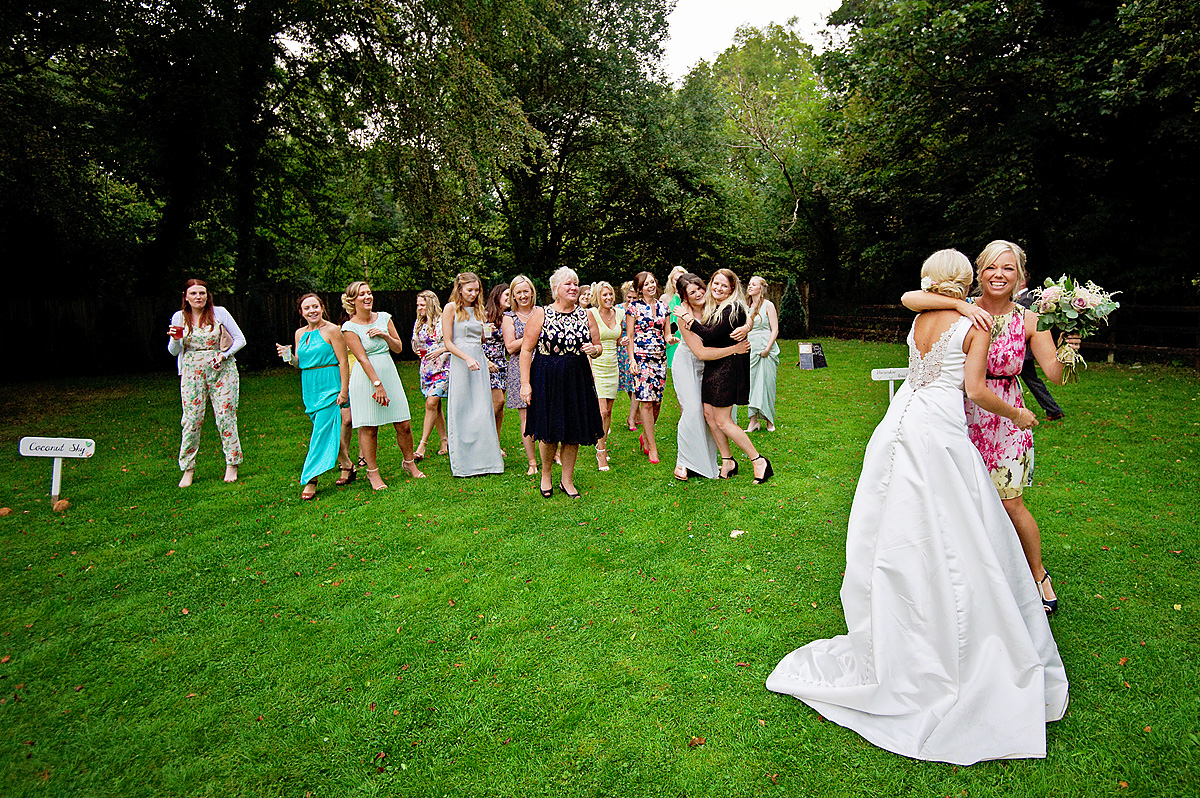 Bride and guest embrace after she catches wedding bouquet