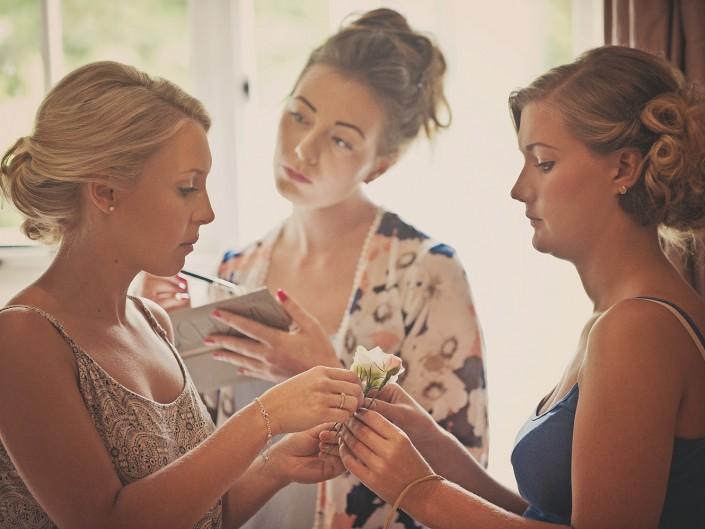 Bride and bridesmaids apply make up whilst getting ready for Tavistock wedding in Devon.