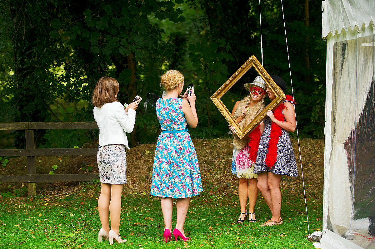 Two wedding guests take photos of friend in picture frame at DIY photobooth