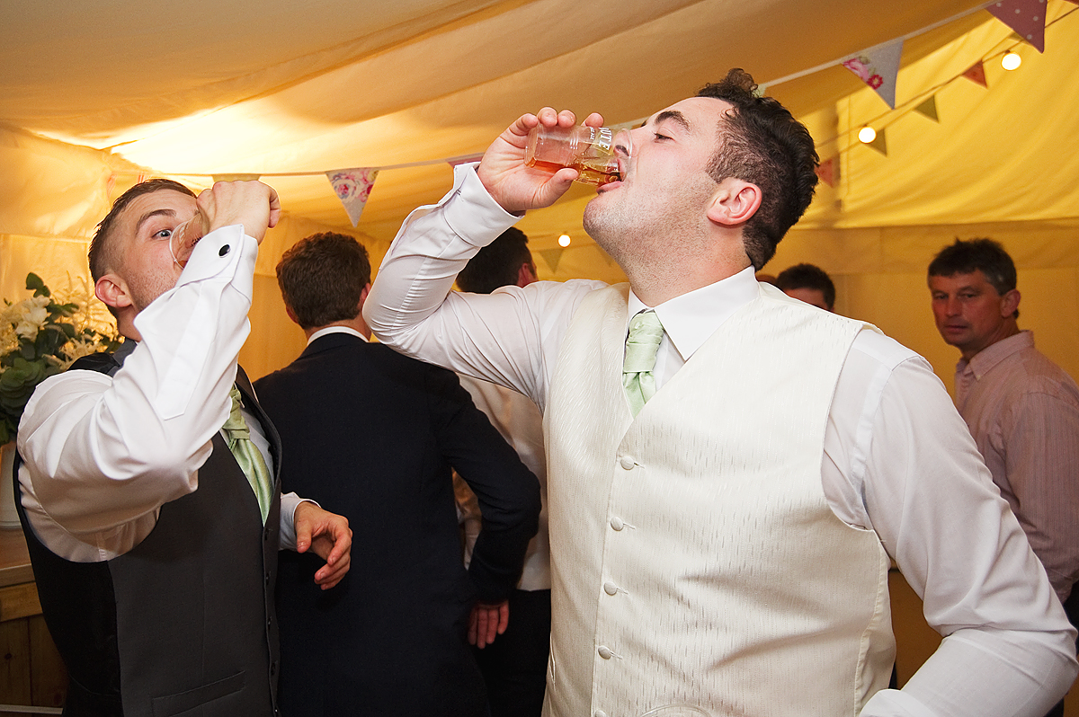 Groom and best man have a shot of booze